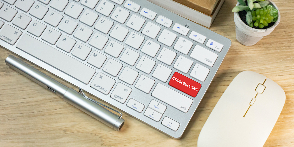 The cyber bullying red button on silver keyboard .
